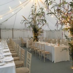 Traditional marquee built by Archers Marquees for a spring wedding in Somerset. It has elephant grey carpet, festoon lighting and trestle tables with limewash chiavari chairs