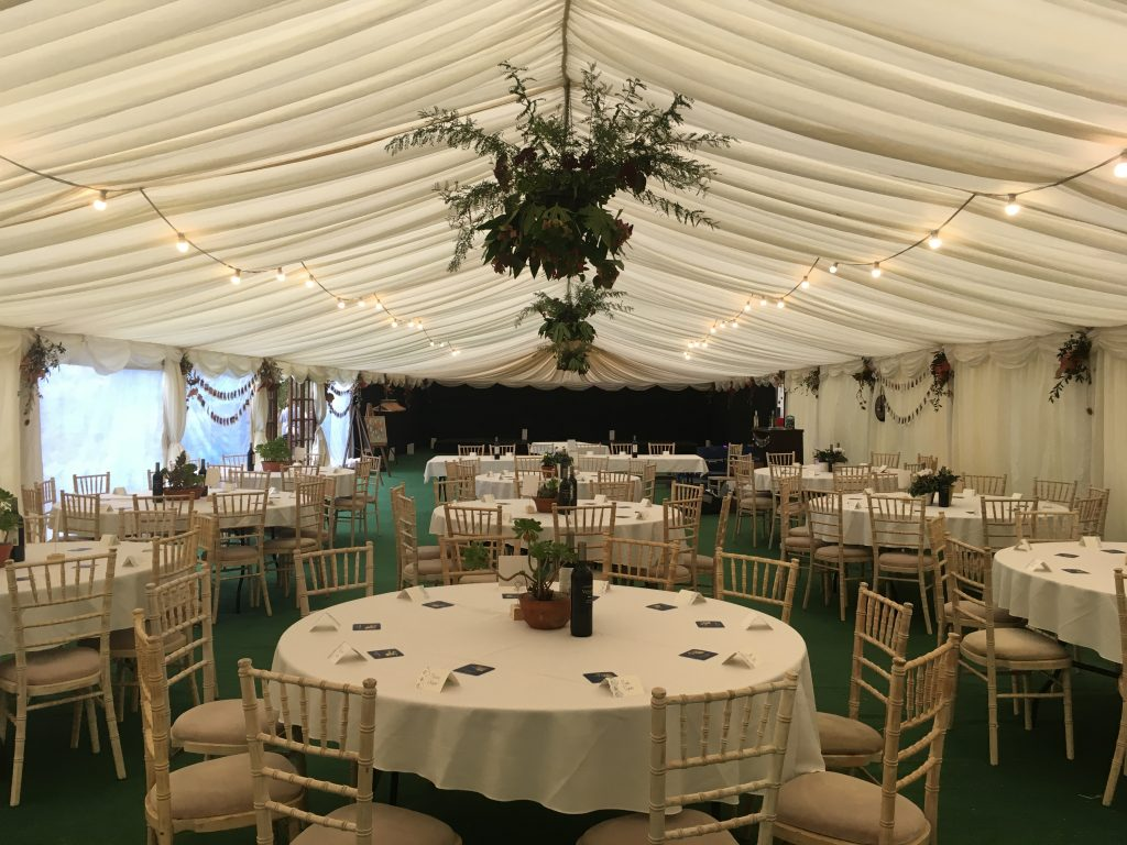 Clearspan wedding marquee with green carpet, ivory lining, round tables and festoon lights