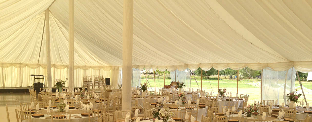 Pleated ivory lining in a traditional wedding marquee