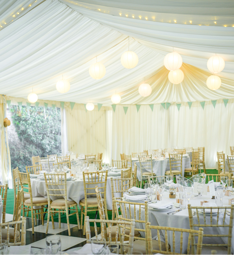 Round tables and limewash chiavari banquet chairs in a clearspan wedding marquee on a 3m leg, built by Archers Marquees for a summer wedding in Somerset