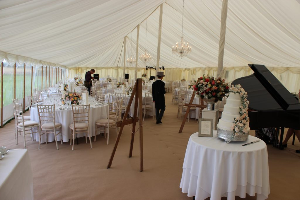 Round cake table in a traditional wedding marquee