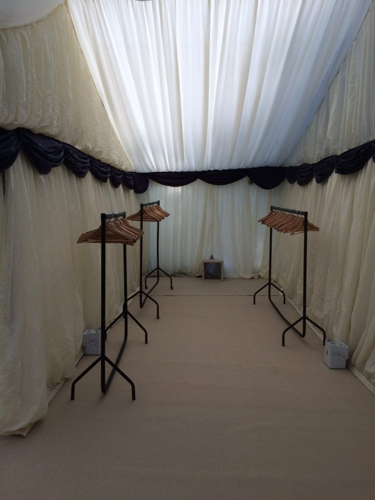 Black metal coat rails with wooden hangers in a clearspan marquee