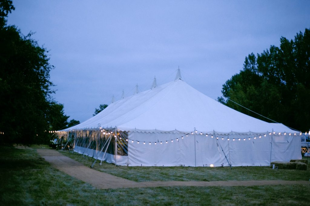 Traditional marquee with coconut matting pathway and festoon lights, for a summer wedding in Bristol