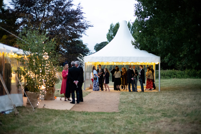 Chinese Hat or Pagoda Marquee being used as a reception area at a summer wedding in Oxford, with a coconut matting pathway leading into the main traditional marquee. Built by Archers Marquees in Oxford