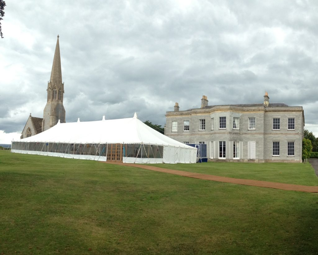 Traditional marquee with double doors and a coconut matting pathway built for a summer wedding in Somerset by Archers Marquees
