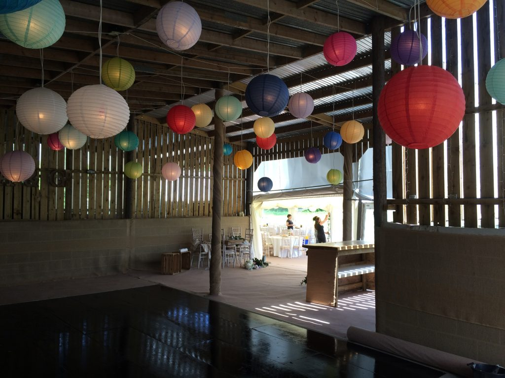 Rustic barn with hanging coloured paper lanterns and a wooden dancefloor, decorated by Archers Marquees for a wedding in Bath