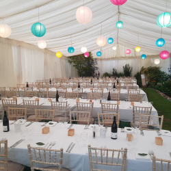 Chiavari chairs with trestle tables in a clearspan marquee decorated with lining and lanterns, for a wedding in Bath