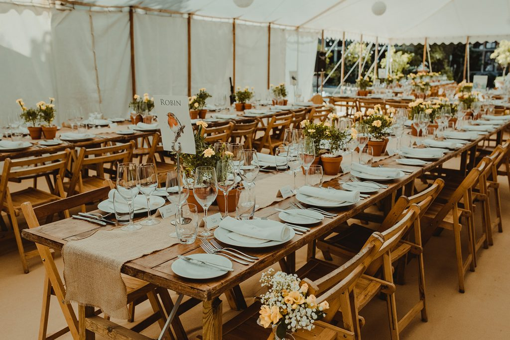Rustic trestle tables with beechwood folding chairs in a traditional wedding marquee