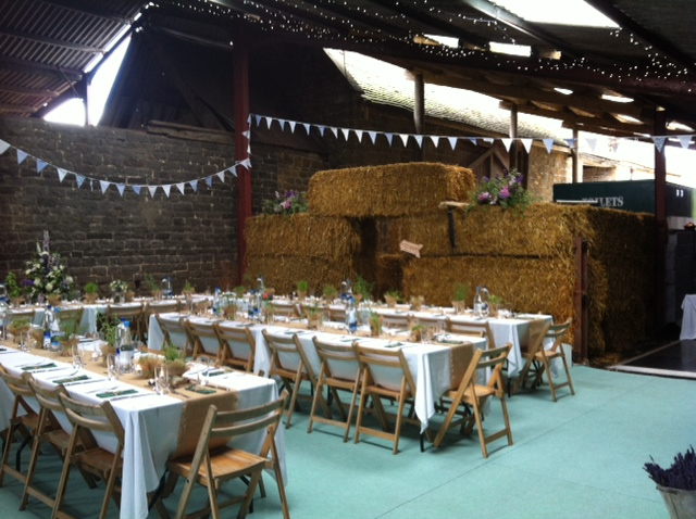 Rustic barn with green carpet and trestle tables