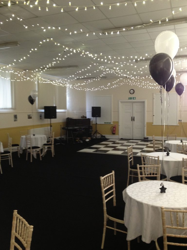 Village Hall with black carpet, fairy lights and a black and white dancefloor