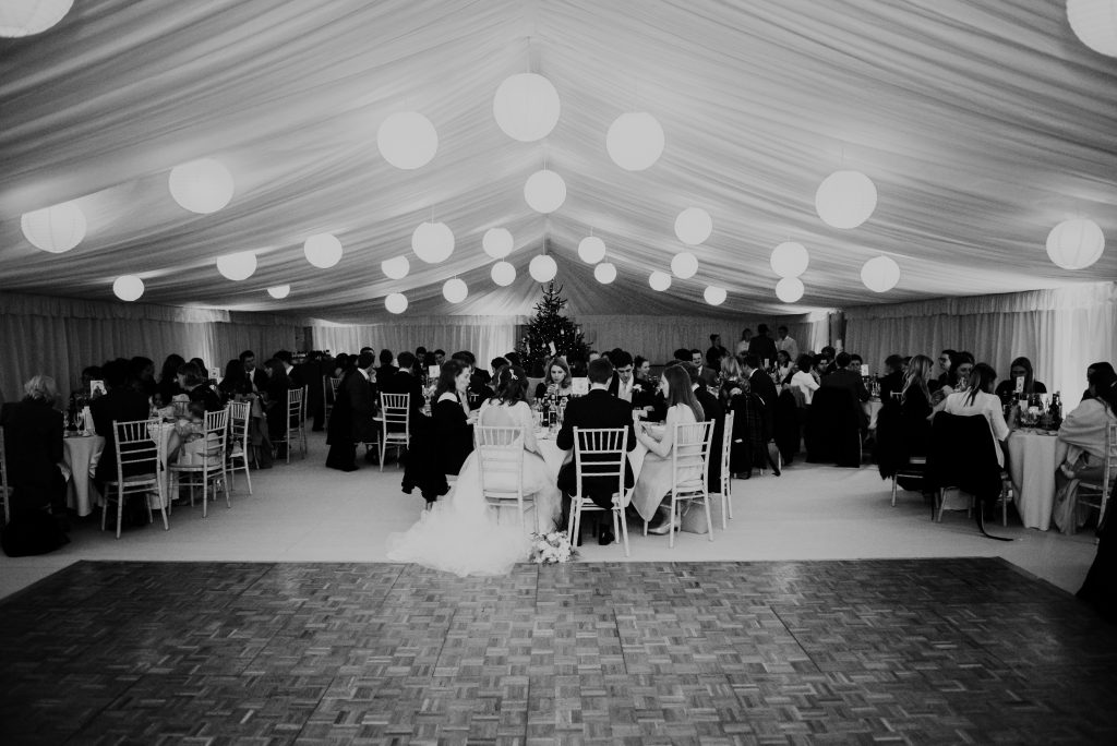 Ivory pleated linings by Archers Marquees in a sports hall in Bath with white paper lanterns, round tables and a wooden parquet dancefloor