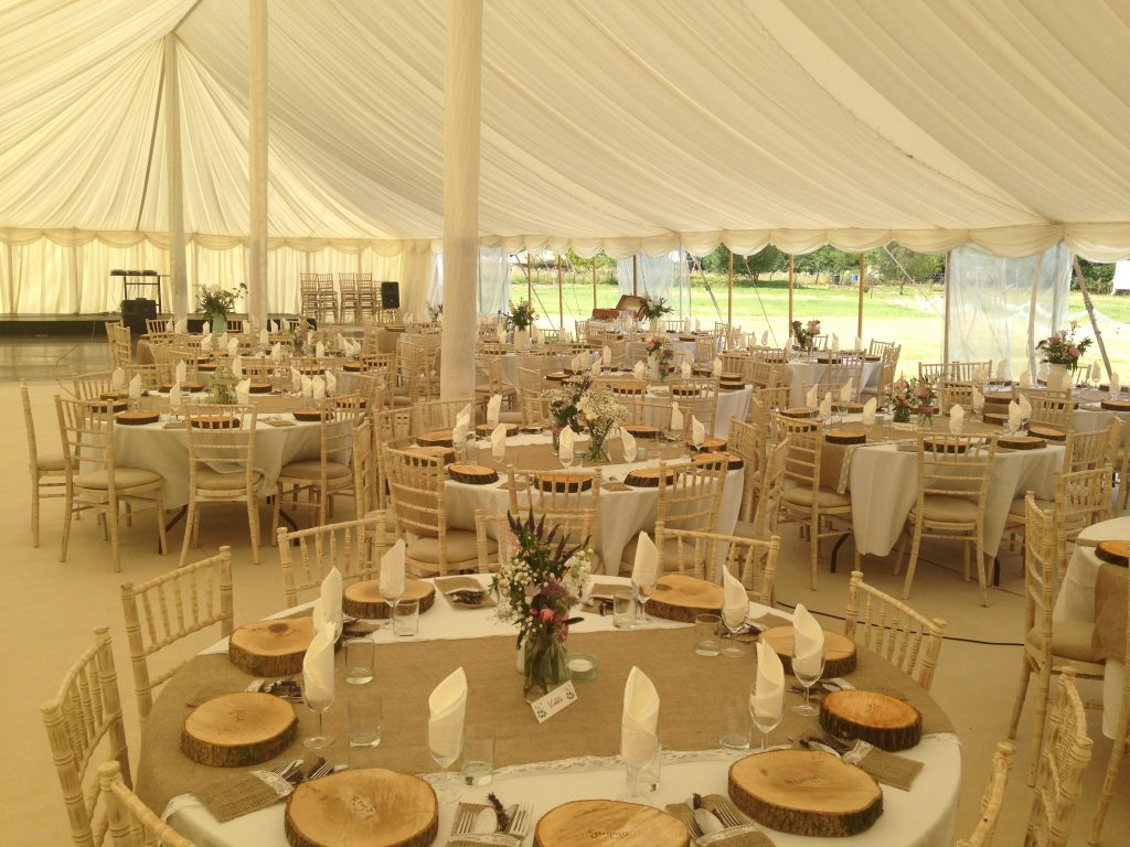 Traditional wedding marquee with cream carpet, ivory lining and round tables