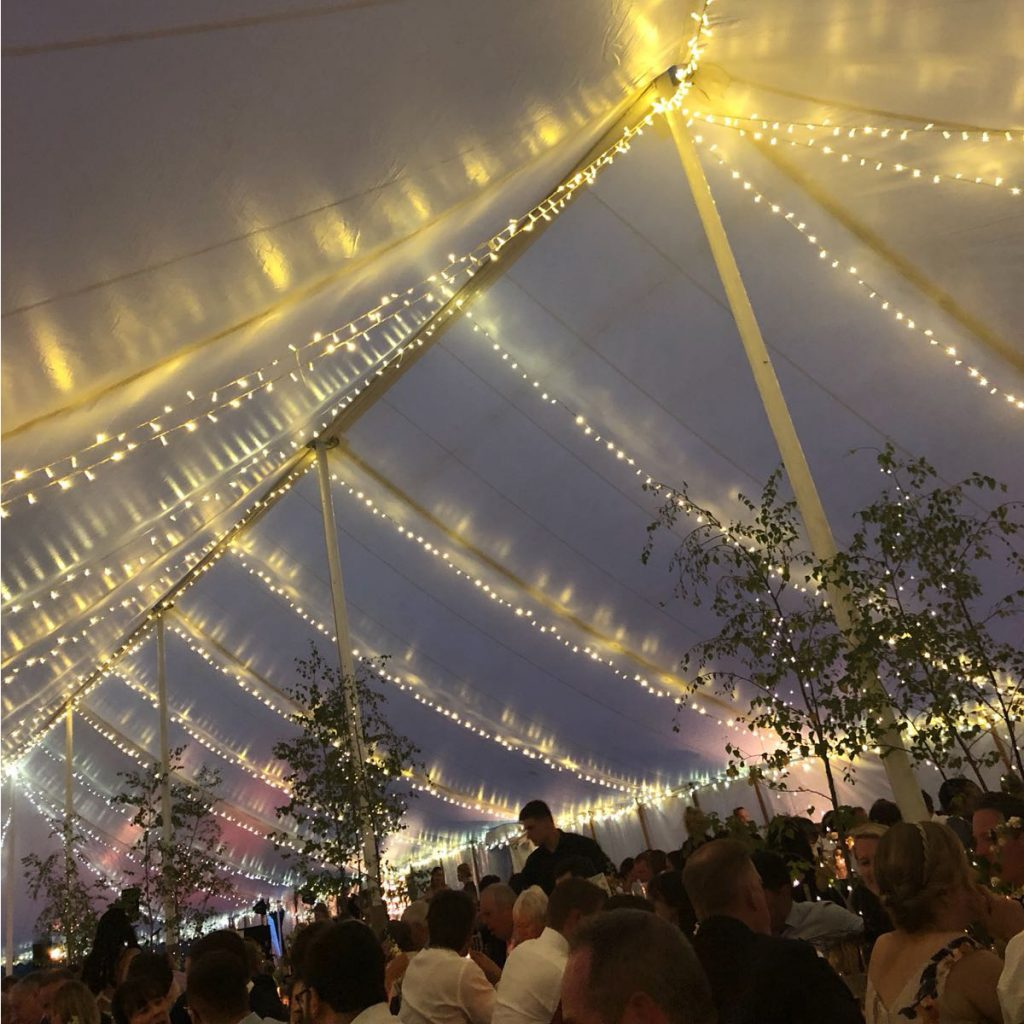 Fairy lights hung in the roof of a traditional wedding marquee