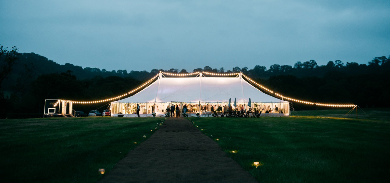 Festoon lighting over the top of a traditional marquee, with a coconut matting pathway provided by Archers Marquees in Somerset