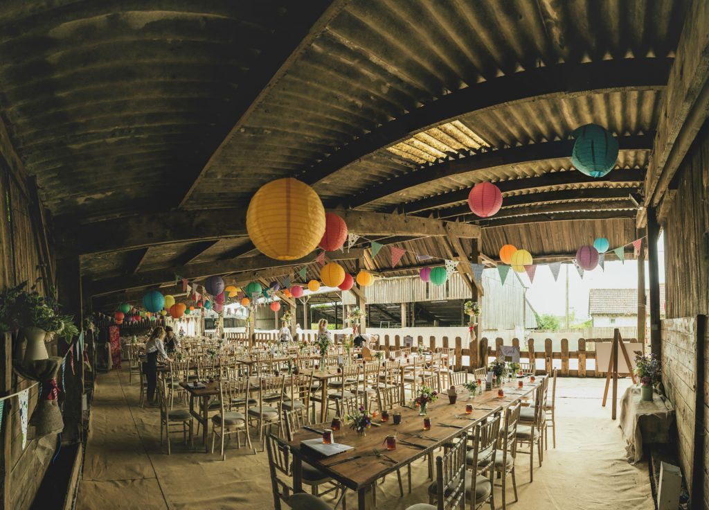 Rustic wedding barn dressed with coloured paper lanterns and bunting
