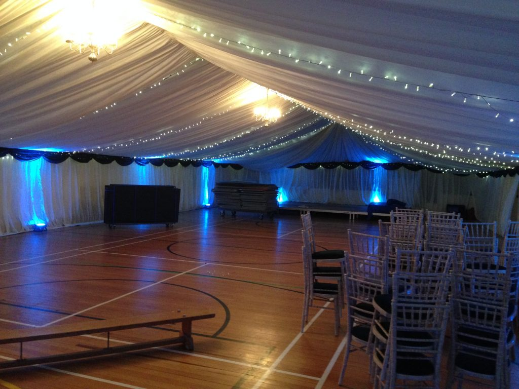 Lined sports hall with chandeliers, uplighters and fairy lights