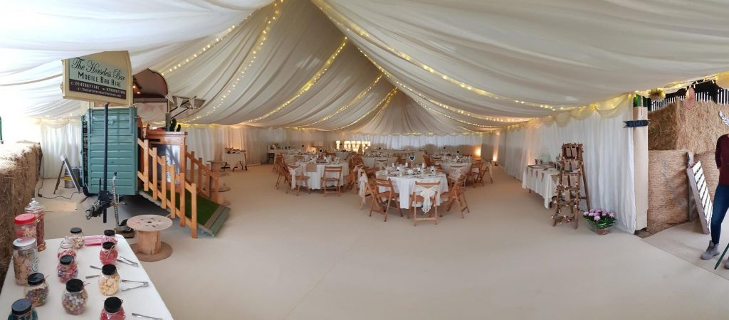 Barn converted for a summer wedding near Glastonbury by Archers Marquees, with ivory linings and fairy lights in the ceiling, and beige carpet on the floor.