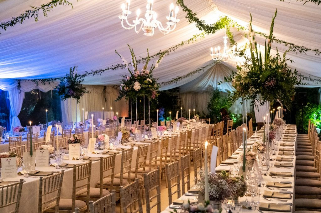 Clearspan wedding marquee with ivory lining, chandeliers and trestle tables for an autumnal wedding in Oxford, built by Archers Marquees