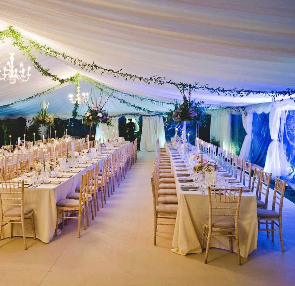 12m Clearspan marquee with ivory linings, hard flooring and beige carpet, with trestle tables and limewash chiavari chairs, built by Archers Marquees in Oxford