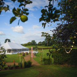 Traditional wedding marquee exterior with coconut matting pathway and outdoor festoon lights on shepherd hooks, for a rustic wedding in Bristol