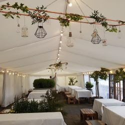 Flat white linings and festoon lighting in a clearspan marquee built by Archers Marquees in Bristol