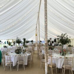 Fairylights wrapped around the pole in a traditional marquee